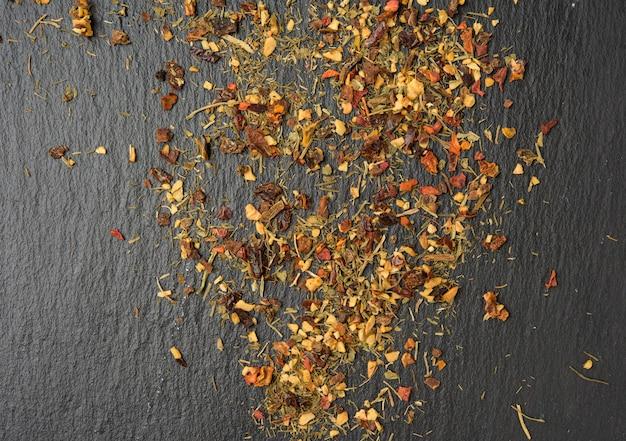 Mélange de diverses épices séchées sur fond noir, vue du dessus