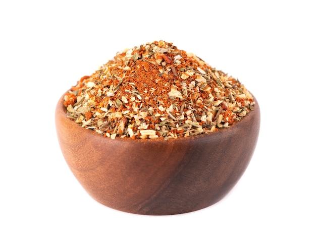Mélange d'épices herbes et tomates sèches dans un bol en bois isolé