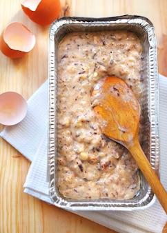 Mélange de farine, œufs, bananes et chocolat noir haché et noix dans un moule en aluminium
