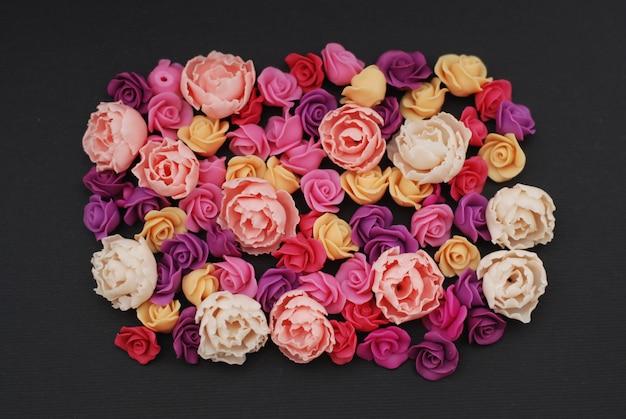 Mélange de fausses fleurs roses, espace de copie noir.