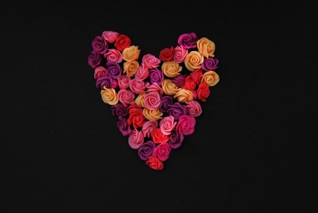 Mélange de fausses fleurs roses en forme de coeur, espace de copie noir.