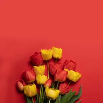 Mélange de fleurs de tulipes printanières sur le rouge.