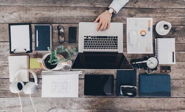 Mélange de fournitures de bureau et de gadgets sur un bureau en bois