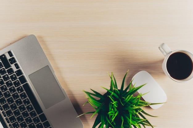 Mélange de fournitures de bureau et gadgets sur un fond de table en bois.