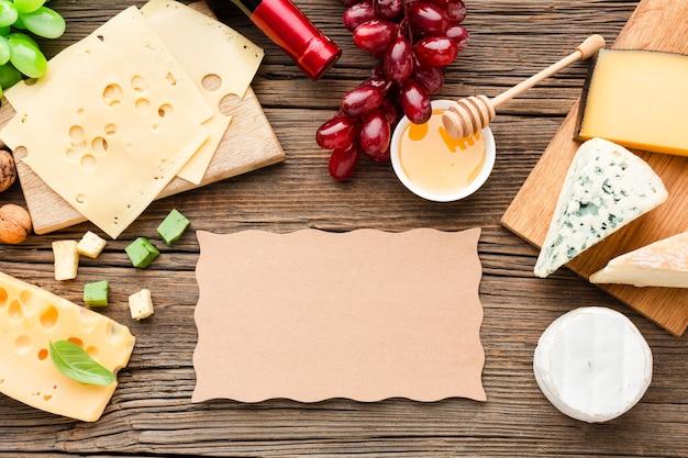 Mélange de fromage plat poser des raisins et du miel avec du carton blanc