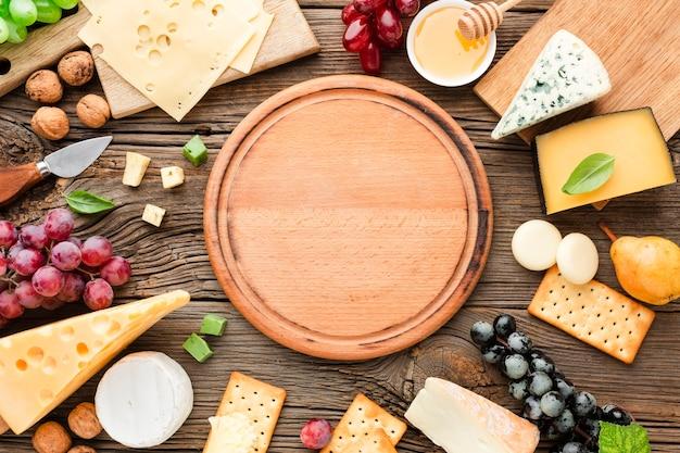 Mélange de fromages plat avec planche à découper en bois