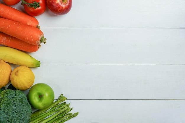 Mélange de fruits et légumes et multicolores sur une table en bois blanc