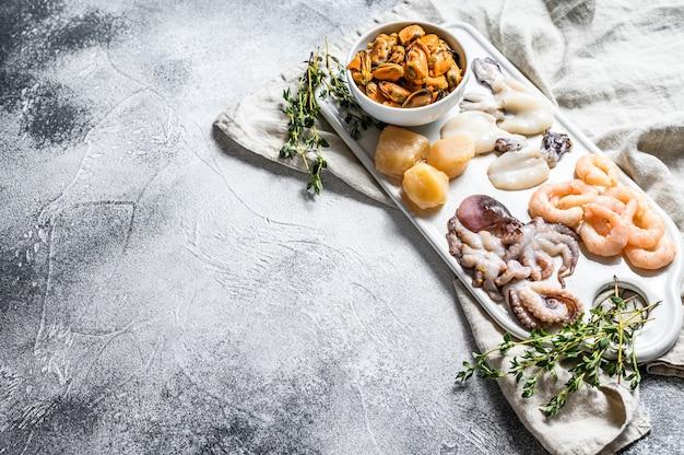 Mélange de fruits de mer crus sur un fond de planche à découper en céramique