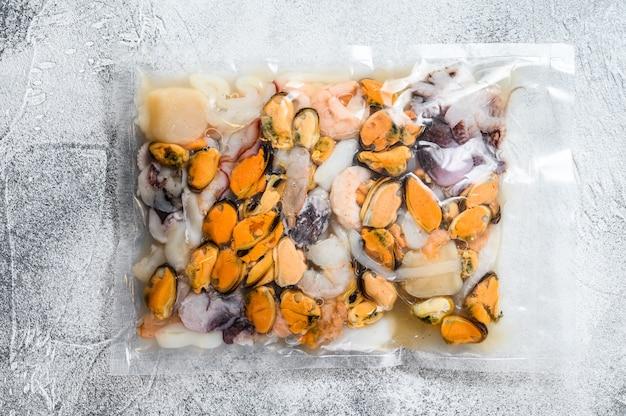 Mélange de fruits de mer crus sous emballage sous vide.