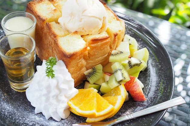 Mélange de fruits et pain au miel avec crème glacée dans un plat noir sur la table