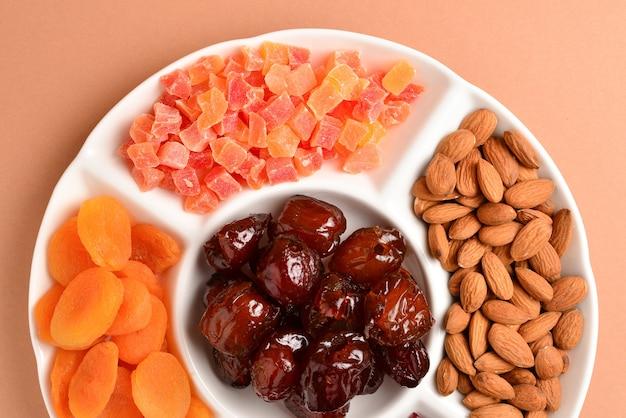 Mélange de fruits secs et de noix sur une plaque blanche. abricot, amande, raisin sec, dattes fruits. sur fond marron. espace pour le texte ou la conception.
