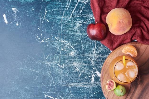 Mélange de fruits avec une tasse de boisson sur bleu.