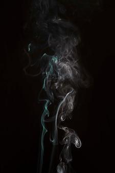 Mélange de fumée verte et blanche sur fond noir