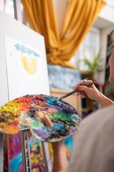 Mélange de gouache colorée. femme talentueuse tenant une palette de couleurs mélangeant la gouache colorée et la peinture