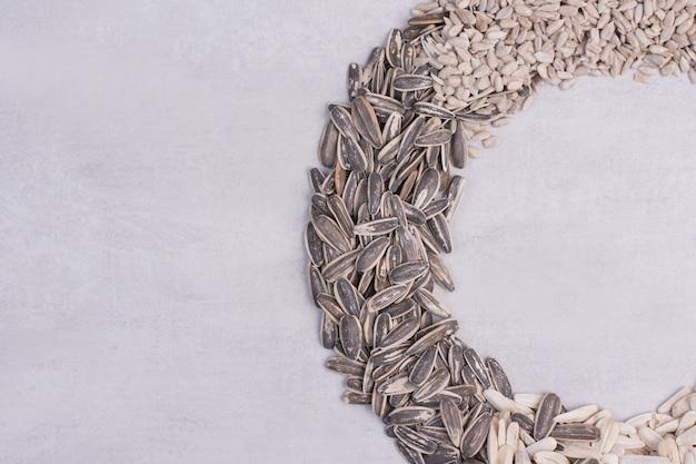 Mélange de graines de tournesol sur une surface blanche.