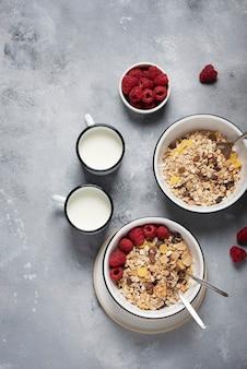 Mélange granola sain avec framboise et lait sur fond gris, vue de haut en bas