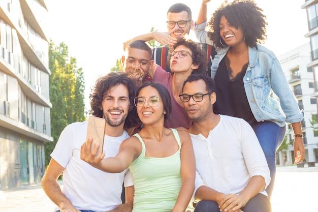 Un mélange joyeux a couru les personnes prenant un groupe selfie
