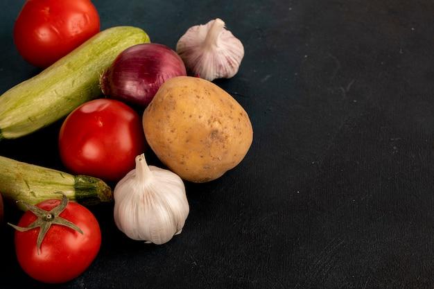 Mélange de légumes comprenant des gants à l'ail, des pommes de terre, des oignons, des courgettes et des tomates sur un tableau noir.