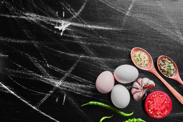 Mélange de légumes et d'épices sur table noire.