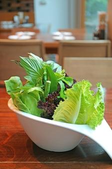 Mélange de légumes frais dans un bol blanc servi sur table en bois