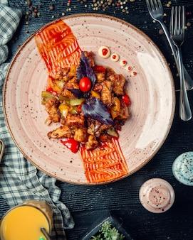 Mélange de légumes frits et viande recouverte de basilic