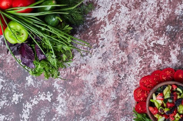 Mélange de légumes isolé sur un morceau de marbre avec une tasse de salade de côté dans les deux coins.