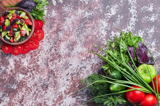 Mélange de légumes isolé sur un morceau de marbre avec une tasse de salade de côté