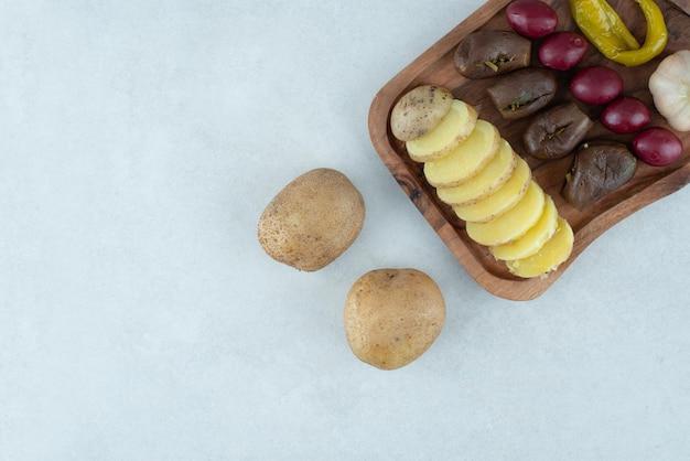 Mélange de légumes marinés et pommes de terre bouillies sur planche de bois.