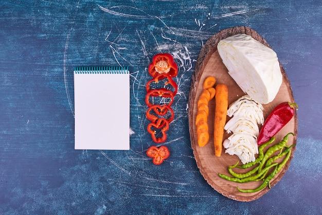 Mélange de légumes sur un plateau en bois avec un cahier de côté.