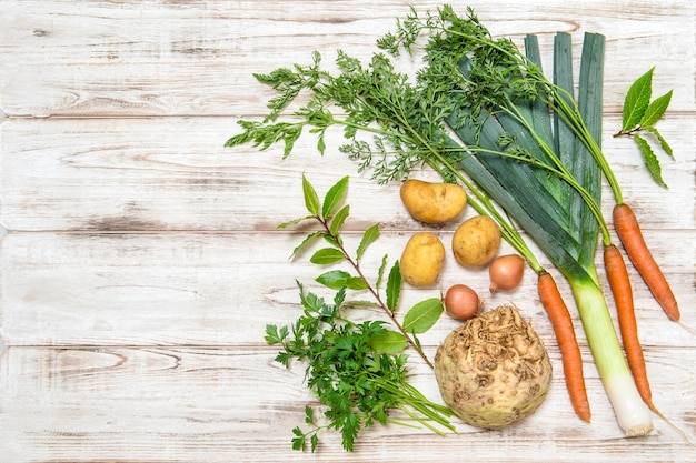 Mélange de légumes pour la préparation de soupe. poireau, carottes, oignon, persil, pommes de terre, céleri-rave, feuilles de laurier. nourriture saine. nutrition biologique fraîche