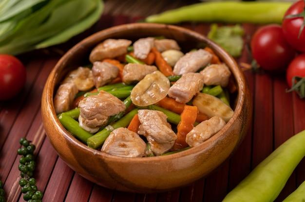 Mélange de légumes sautés contenant des pois verts, des carottes, des champignons, du maïs, du brocoli et du porc