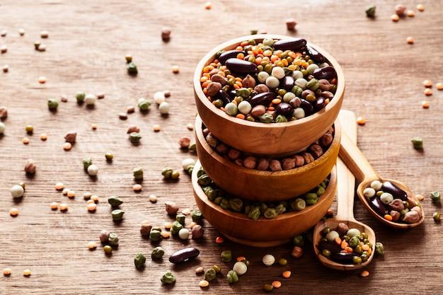 Mélange de légumineuses indiennes séchées crues dans des bols en bois sur fond rustique.