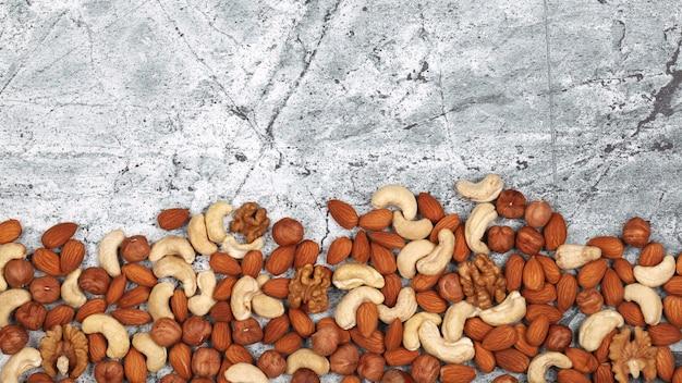 Mélange de noix brutes sur fond de pierre grise.