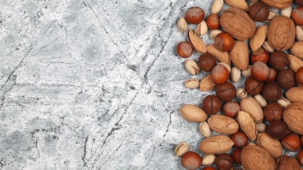 Mélange de noix en coque crues sur fond de pierre grise.