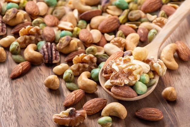 Mélange de noix sur une cuillère en bois, assortiment et divers de noix alimentation saine.