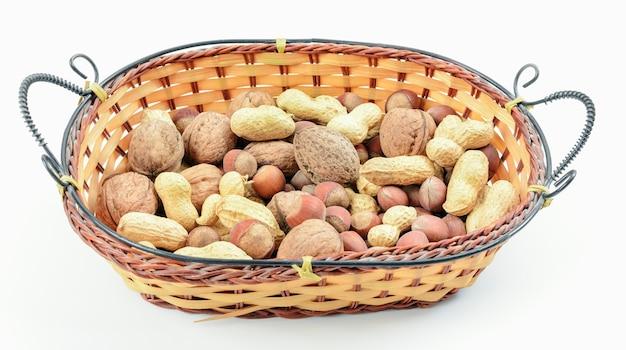 Mélange de noix dans un panier en osier sur fond blanc. le concept d'une bonne nutrition.