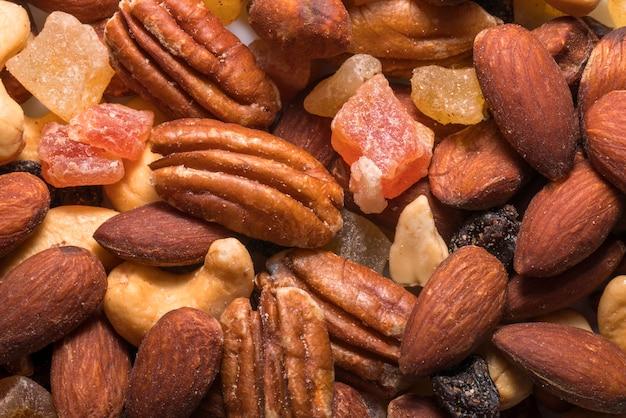 Mélange de noix sur fond blanc assortiment de noix et raisins secs en gros plan