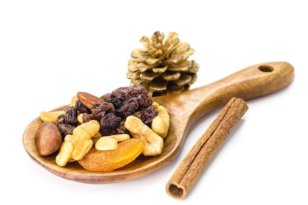Mélange de noix et de fruits de noël déshydratés dans une cuillère en bois rustique. noix du brésil, abricots, raisins secs, pruneaux et noix