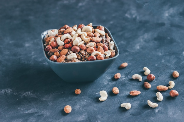 Mélange de noix, noix de cajou, noisettes et amandes dans un bol en céramique sur un fond de béton bleu dans un style sombre