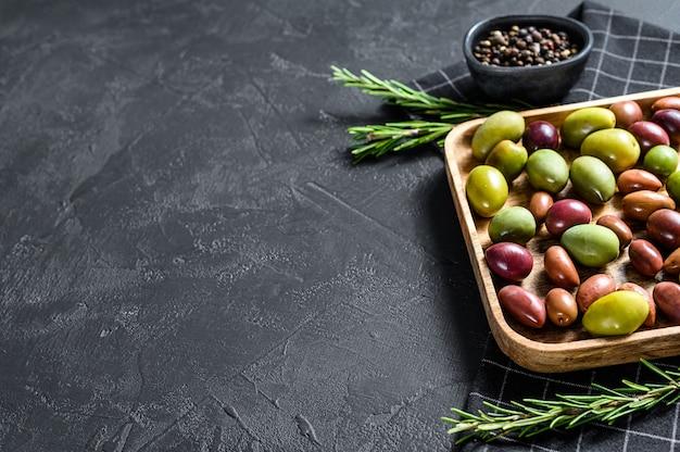 Mélange d'olives marinées colorées avec un os. fond noir. vue de dessus. espace pour le texte