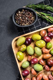 Mélange d'olives salées colorées avec un os. fond noir. vue de dessus