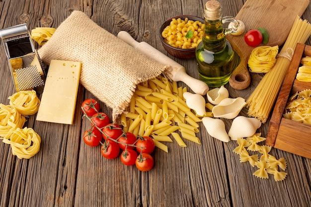 Mélange de pâtes non cuites avec tomates, huile d'olive et fromage à pâte dure