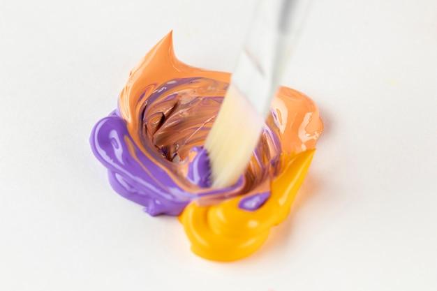 Mélange de peinture pourpre et orange sur un tableau blanc