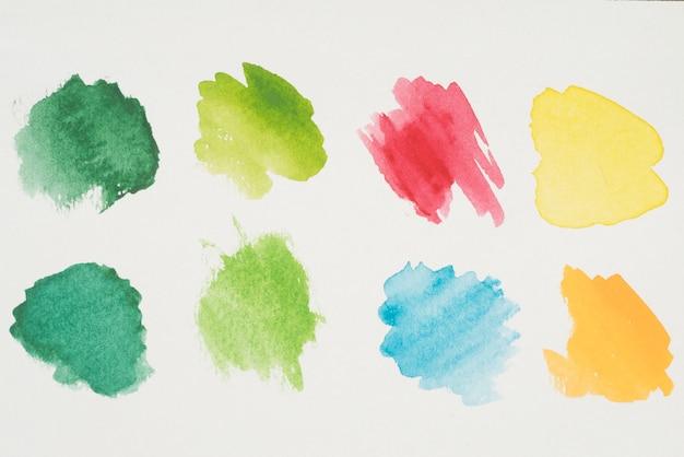 Mélange de peintures jaune, verte, azur, rouge et orange sur papier blanc
