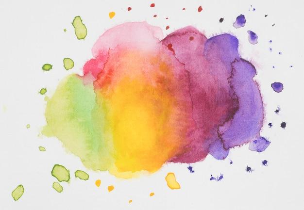 Mélange de peintures rose, jaune, violet et vert sur papier blanc