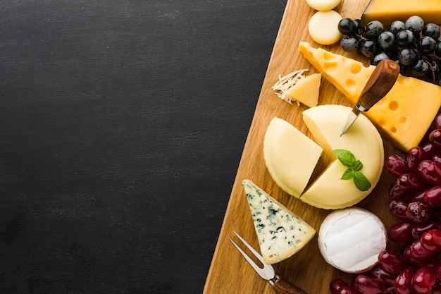 Mélange plat de fromage gastronomique et de raisins sur une planche à découper avec espace pour copie