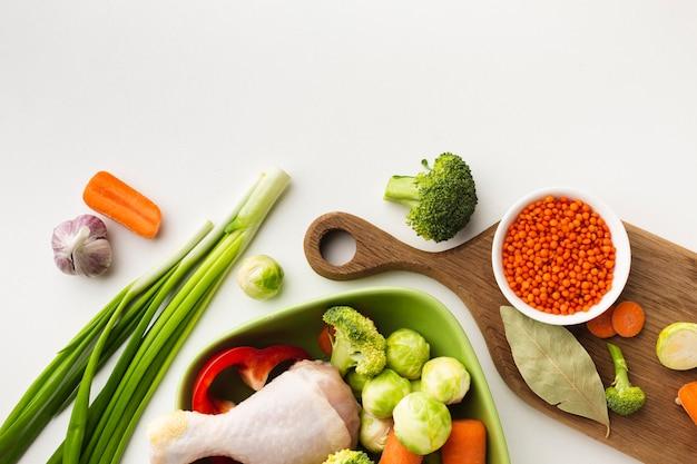 Mélange plat de légumes sur une planche à découper et dans un bol avec une baguette de poulet et une cuillère