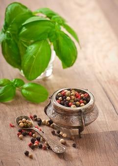 Mélange de pois poivrons dans un vieux bol et de feuilles de basilic