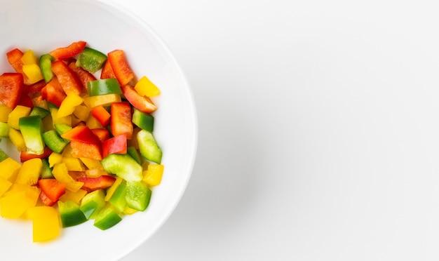 Mélange de poivrons rouges jaunes et verts crus coupés en petits morceaux mis dans un bol