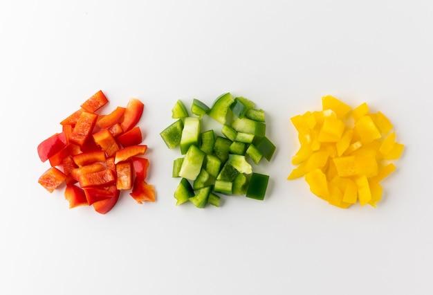 Mélange de poivrons rouges jaunes et verts crus coupés en petits morceaux